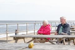 Senior couple sitting on the seaside table bench looking over the Southwold beach royalty free stock photo