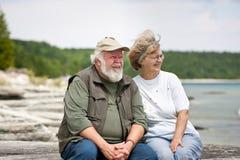 Senior couple sitting at shores edge Stock Photo
