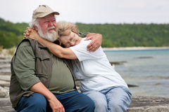 Senior couple sitting at shores edge Royalty Free Stock Image