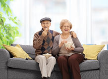 Senior couple sitting on a sofa and eating popcorn stock photos