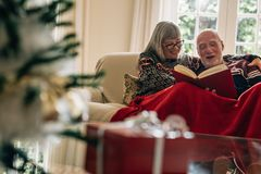 Senior couple sitting on a sofa enjoying reading a book with a gift box in the foreground. Smiling couple spending time together. Reading a book covering stock photos