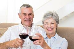 Senior couple sitting on sofa having red wine Stock Photo