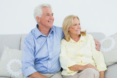 Senior couple sitting on sofa while looking away Stock Photo