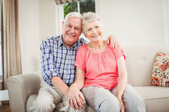 Senior couple sitting on sofa and smiling Royalty Free Stock Photos