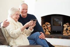 Senior Couple Sitting On Sofa Taking Selfie Stock Photos