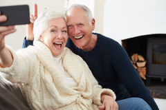 Senior Couple Sitting On Sofa Taking Selfie Stock Photo