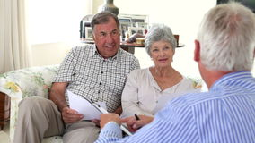 Senior Couple Sitting On Sofa Talking To Financial Advisor