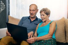 Senior couple sitting in sofa and using laptop together stock photos