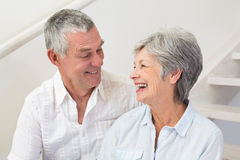 Senior couple sitting on stairs smiling at each other Royalty Free Stock Image