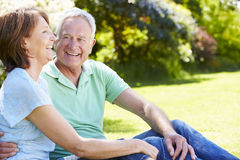 Senior Couple Sitting In Summer Garden Together Stock Images
