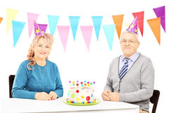 Senior couple sitting on table with big cake and celebrating bir Stock Photo