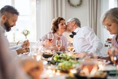 A senior couple sitting at a table on a indoor birthday party, kissing. A senior couple sitting at a table on a indoor birthday party, kissing when eating stock images
