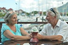 Senior couple sitting on  table on the pier. Happy cute senior couple sitting on the table on the pier Stock Photos