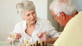 Senior couple sitting at table playing chess. At home in the kitchen stock video footage