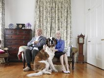 Senior Couple Sitting With Their Pet Dog Stock Image