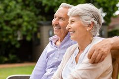 Senior couple sitting on bench stock photo