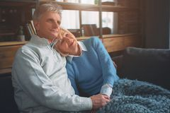 Senior couple are sitting together on the couch. She has put her royalty free stock image