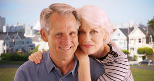 Senior couple sitting together at the park and smiling at camera Stock Image