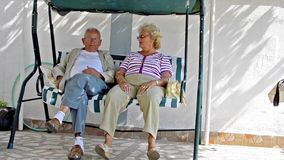 Senior couple sitting together and resting. Senior couple sitting together talking, resting and having fun Stock Video. Mature retired couple grandfather and stock footage