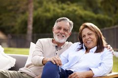 Senior couple sitting together on a seat in the garden smiling to camera, front view royalty free stock images