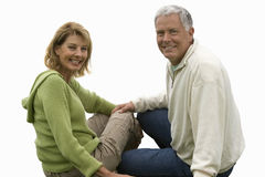 Senior couple sitting together, smiling, cut out Royalty Free Stock Images