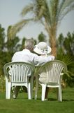 Senior couple sitting at tropic hotel garden Stock Images