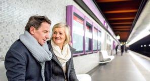 Senior couple sitting at the underground platform, waiting Royalty Free Stock Photography