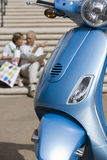 Senior couple sitting on urban steps with street map, man pointing, focus on blue motor scooter parked in foreground Royalty Free Stock Photography