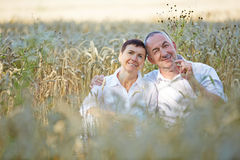 Senior couple sitting in a wheat field Stock Image