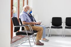 Free Senior Couple Sitting With Face Masks In A Bright Waiting Room Of  A Hospital Or An Office Royalty Free Stock Photo - 190020085