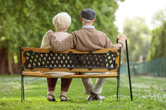 Senior couple sitting on a wooden bench in the park Stock Photos