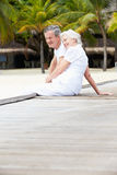 Senior Couple Sitting On Wooden Jetty Royalty Free Stock Photo