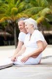 Senior Couple Sitting On Wooden Jetty Stock Photo