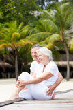 Senior Couple Sitting On Wooden Jetty Royalty Free Stock Photos