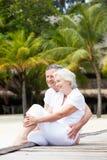 Senior Couple Sitting On Wooden Jetty Royalty Free Stock Photos