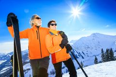 Senior Couple Skiing. Active senior couple skiing, enjoying a clear winter day royalty free stock photography