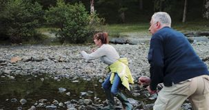 Senior Couple Skimming Stones on the Lake. Senior couple are skimming stones together on a lake while out hiking the Lake District stock video footage