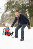 Senior Couple Sledging Through Snowy Woodland Royalty Free Stock Photography