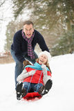 Senior Couple Sledging Through Snowy Woodland Stock Photos