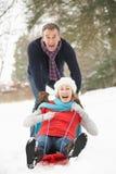 Senior Couple Sledging Through Snowy Woodland Stock Photo