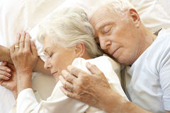 Senior Couple Sleeping In Bed Stock Photography