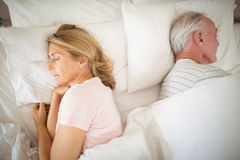 Senior couple sleeping on bed stock photo