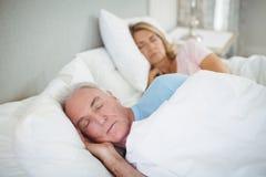 Senior couple sleeping on bed Stock Photos