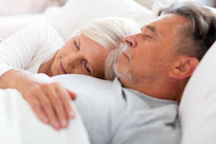 Senior couple sleeping in bed. Senior couple lying in bed together Royalty Free Stock Image