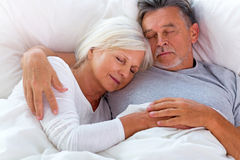 Senior couple sleeping in bed. Senior couple lying in bed together Royalty Free Stock Photography