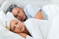 Senior couple sleeping in bed. Senior couple lying in bed together Royalty Free Stock Images