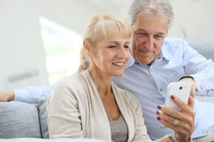 Senior couple with smartphone at home royalty free stock images