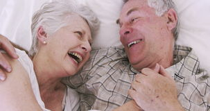 Senior couple smiling in bed stock footage