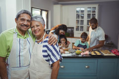 Senior couple smiling at camera while family members preparing dessert in background stock photos