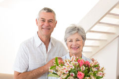 Senior couple smiling at camera holding bouquet of flowers Royalty Free Stock Photos
